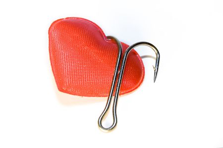 Red heart with a fishing hook on a white background