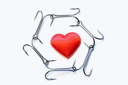 The red heart surrounded with a chain of hooks