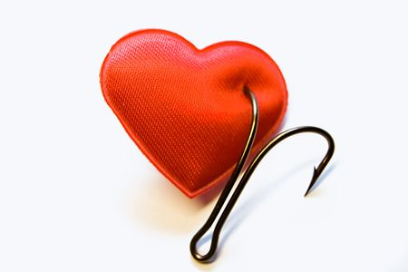 The red heart pinned on a fishing hook Stock Photo