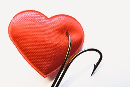get in shape: The red heart pinned on a fishing hook Stock Photo