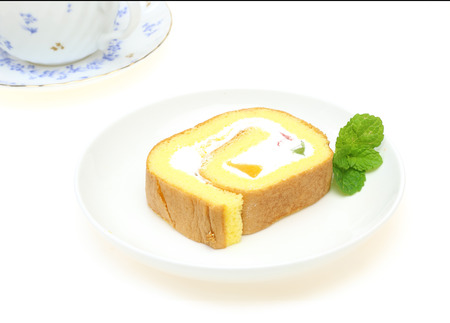 swiss roll: Swiss roll on a plate with a tea cup