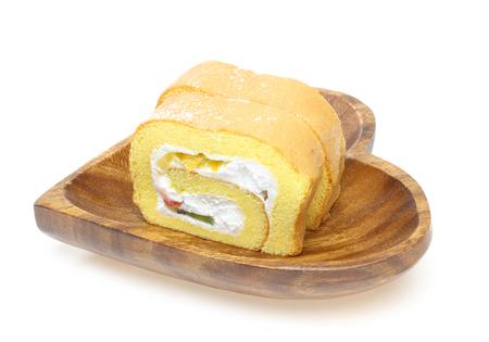 swiss roll: Swiss roll on a wooden plate Stock Photo