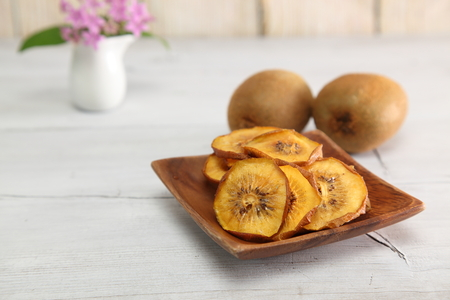 Dried kiwi fruit in a wooden bowl