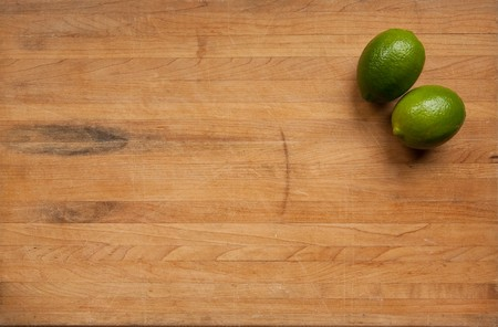 A pair of limes sit in the corner of a worn butcher block cutting board Stock Photo - 6930029