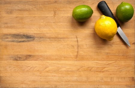 A pair of limes and a lemon sit with a knife in the corner of a butcher block cutting board