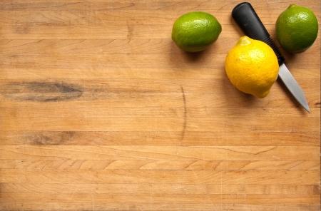 contadores: Un par de limas y un lim�n sentarse con un cuchillo en la esquina de una tabla de cortar de bloque de carnicero