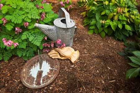 sundial: An old sundial sits in a garden next to a worn watering can and leather work gloves