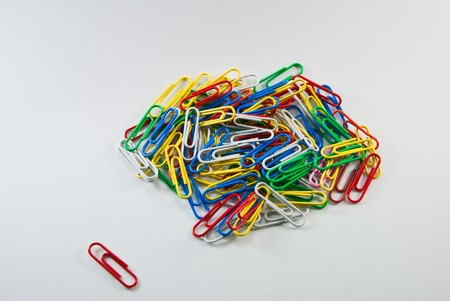 A single paperclip sits apart from a larger group of colorful paperclips photo