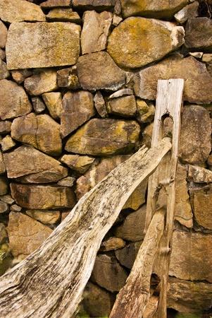 split rail: A wooden split rail fence ends at a stone rock wall
