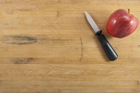 paring: A red delicious apple sits next to a paring knife on a worn cutting board Stock Photo