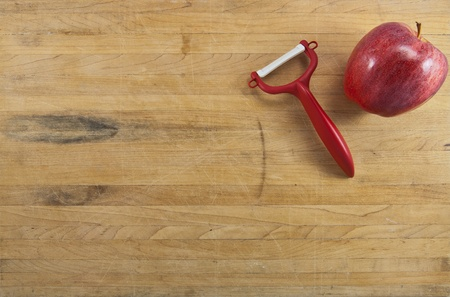 A red delicious apple sits next to a red peeler ona worn butcher block counter photo
