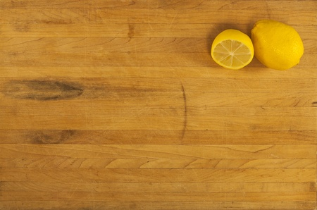 A whole and half lemon sit in the corner of a butcher block counter photo