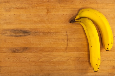 A pair of bananas sit on a worn butcher block counter photo