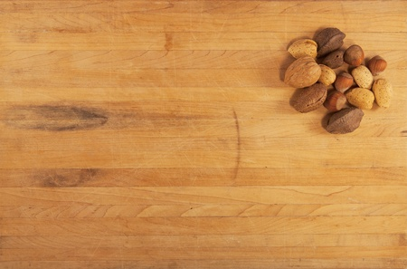 A pile of mixed nuts sit on a worn butcher block counter photo