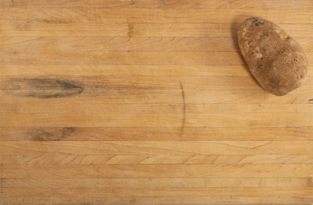 russet potato: A russet potato sits on a worn butcher block counter Stock Photo