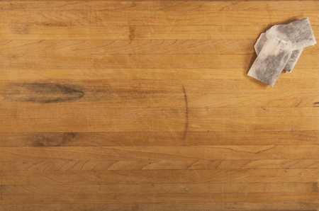 A pile of tea bags sit on a butcher block counter photo