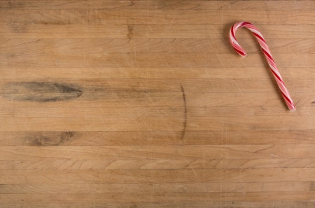 A candy cane sits on a worn butcher block cutting board with room for text photo