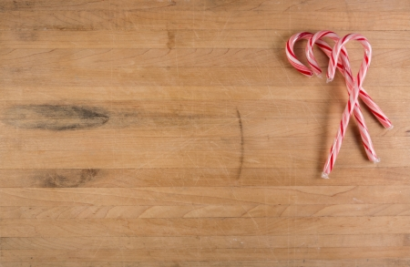 Three candy canes sits on a worn cutting board with room for text  photo