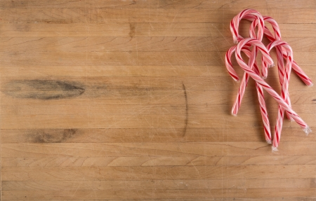 A grouping of candy canes sits on a worn butcher block cutting board photo