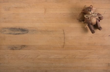 A carved teddy bear angle sits on a worn butcher block counter Stock Photo - 16928764