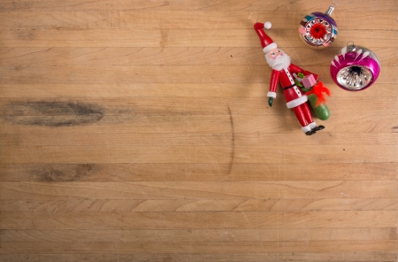 A grouping of traditional Christmas ornaments sits on a worn butcher block countertop photo