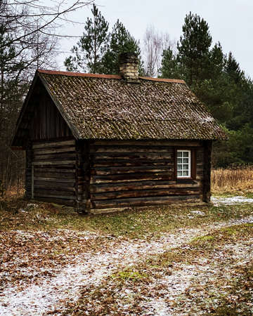 Wooden sauna log house in the woods in winter. Distinctly brown wood. Orange autumn leaves and a little snow on the road can be seen on the road.