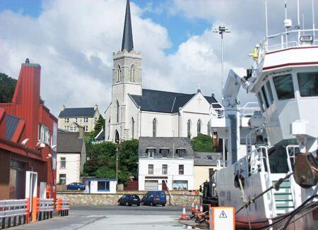 Church between Large fishing trawlers at Killybegs Harbour Coa