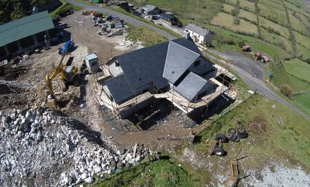 House with scaffolding around its walls being built roof beside the road in the countryside in Ireland