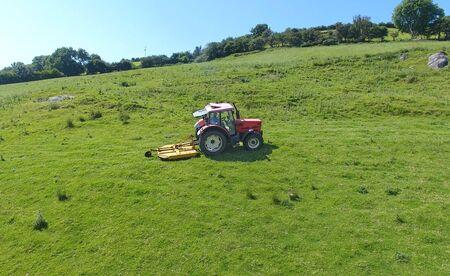 Tractor topping grass in a field Foto de archivo