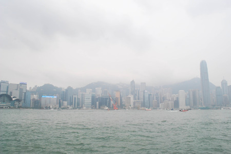 HONG KONG -on  JULY 14, 2012: In a misty or foggy day,View of skyscrapers with boats in the foreground from Victoria bay. Hong Kong