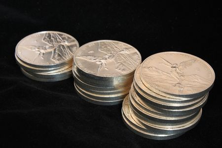 silver coins: growth pile of pure silver coins from mexico named onza libertad Stock Photo
