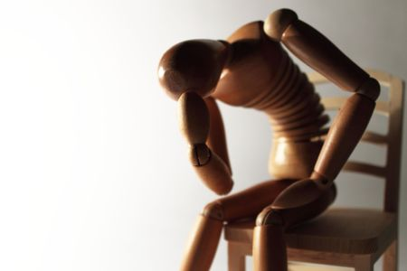 preoccupation: worried wooden dummy sitting with copy space Stock Photo