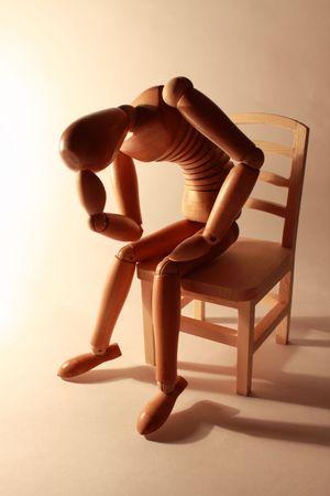 wooden figure: worried wooden dummy sitting