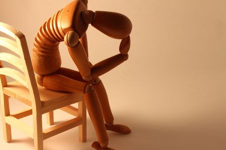 worried wooden dummy sitting with copy space Stock Photo - 5744252