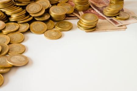 mucho dinero: muchas monedas de oro sobre fondo blanco, moneda mexicana de diez pesos Foto de archivo