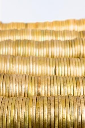 piles of golden coins on white, mexican ten pesos coins photo