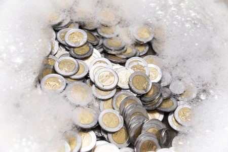 conceptual image of money laundering, mexican pesos coins with soap foam
