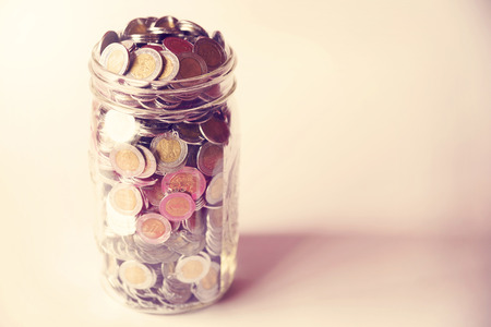 glass jar with full of mexican pesos coins with vintage color tone process Stock Photo
