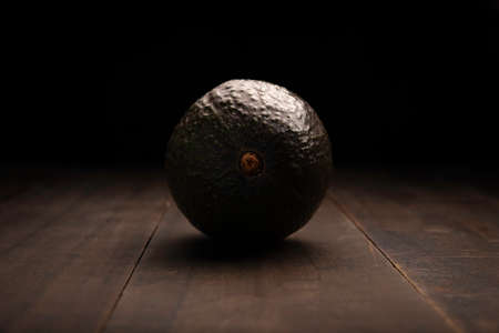 image of avocado close up on rustic wooden surface and black background Zdjęcie Seryjne