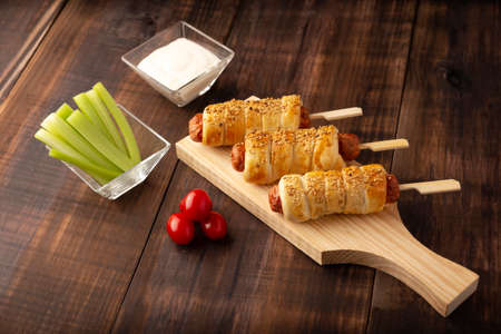 delicious snack of sausages wrapped in puff pastry with sesame seeds accompanied by cherry tomatoes, celery sticks and sauce. Served on wooden board Stock Photo