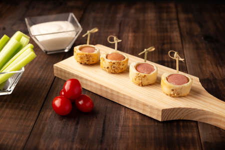 delicious snack of sliced sausages bites wrapped and in puff pastry with sesame seeds accompanied by cherry tomatoes, celery sticks and sauce. Served on wooden board