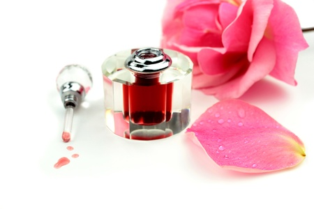 Perfume and pink rose on white background photo