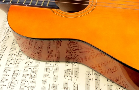 Guitar on music score and note reflection photo