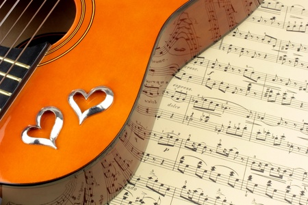 popular music: Guitar, silver hearts and note reflection Stock Photo