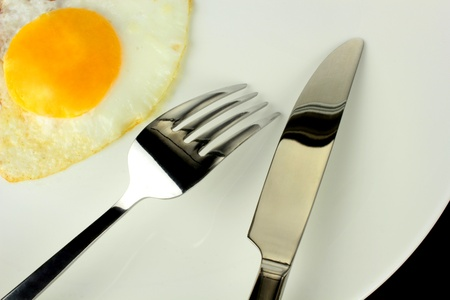 omelet: Fried egg with  fork and knife on a plate  Stock Photo
