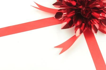 lazo regalo: Cinta roja sobre fondo blanco