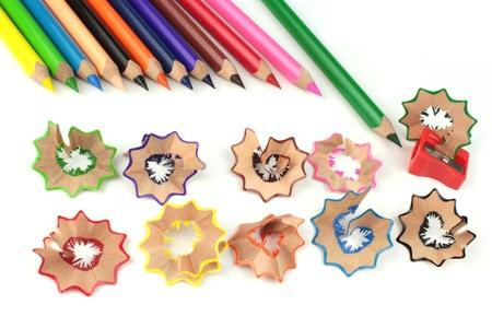 Lápices de colores y sacapuntas en el fondo blanco