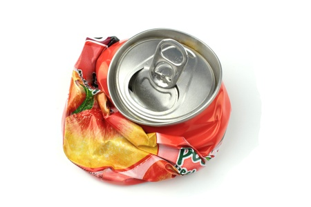 Crushed drink can on white background photo