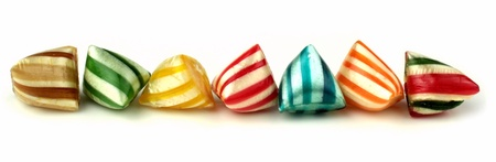 Colorful striped hard candies banner on a white background