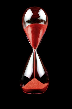 Hourglass with red sand on black background